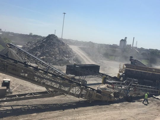 "A ""concrete crusher"" at work near I-696 in Macomb County last May as part of the freeway reconstruction project. Warren Mayor Jim Fouts said heavy pounding and excavation caused rats to try to flee to nearby neighborhoods."
