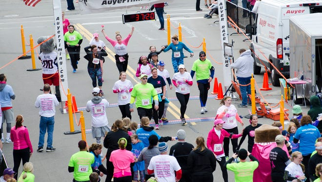Racers in the annual Komen Twin Tiers Race for the Cure cross the finish line in downtown Elmira in 2016.