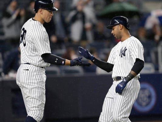New York Yankees' Aaron Hicks, right, celebrates with Aaron Judge after hitting a solo home run during the eighth inning of the baseball game against the Chicago White Sox at Yankee Stadium, Wednesday, April 19, 2017, in New York. The Yankees defeated the White Sox 9-1. (AP Photo/Seth Wenig)