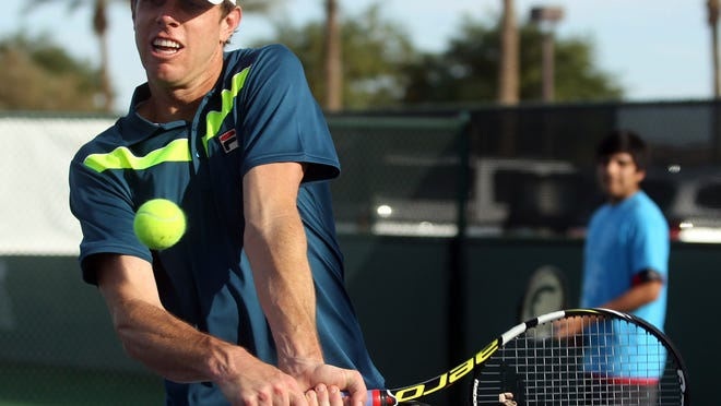 Professional tennis player Sam Querrey returns the ball in a hitting drill during the Fila Junior Tennis Clinic on Tuesday, March 10, 2015 at the BNP Paribas Open. High school tennis players from Desert Mirage, Coachella Valley, and Palm Springs High Schools attended the clinic.