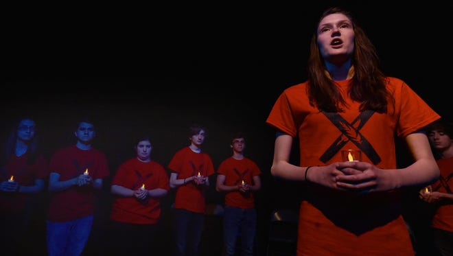 "Sophia Friedenfels narrates as she leads a candlelight vigil with, from left, Jemma Benton, Connor Werkheiser, Megan Schaut, Ian Toyne, Dominic DiCarlo and Robert Puccini in a scene from the StageKids production of ""The Laramie Project'' at Third Avenue Playhouse."