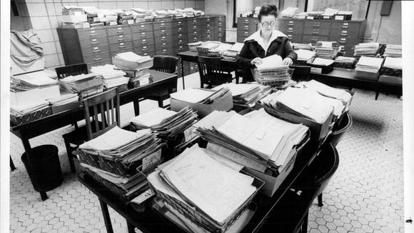 The Monroe County Clerk's office, circa 1978. Virginia Crane, supervisor of the civil section, is surrounded by stacks of unfiled legal papers. The office is five months behind on filing.