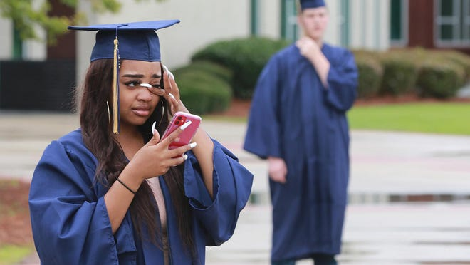 Mickey Kimbrough gets emotional when she takes a call from her boyfriend Dimyas Perdue who is in Virginia and will watch her graduate via cell phone as graduates of Northside High School accompanied by family and friends received their diplomas then gathered for a few moments to take some special photos.