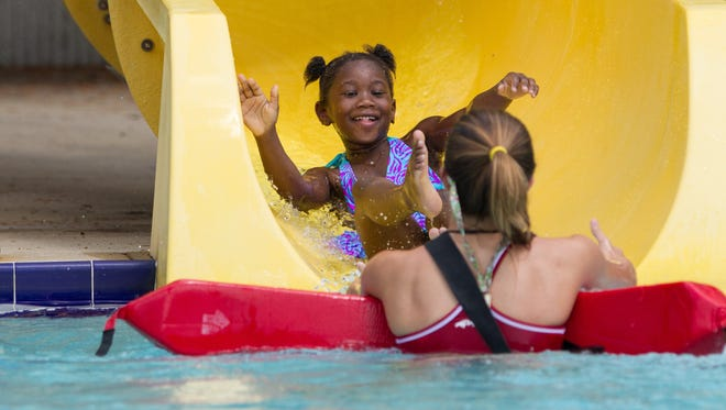 Sydney Williams, 6, slides in to the arms of 17-year-old lifeguard Haley Jacobs at the Trousdell Aquatics Center on Tuesday.
