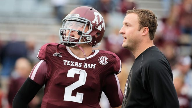 COLLEGE STATION, TX - NOVEMBER 09: Johnny Manziel #2 of the Texas A&M Aggies chats with his quarterback coach Jake Spavital before the game against the Mississippi State Bulldogs at Kyle Field on November 9, 2013 in College Station, Texas.