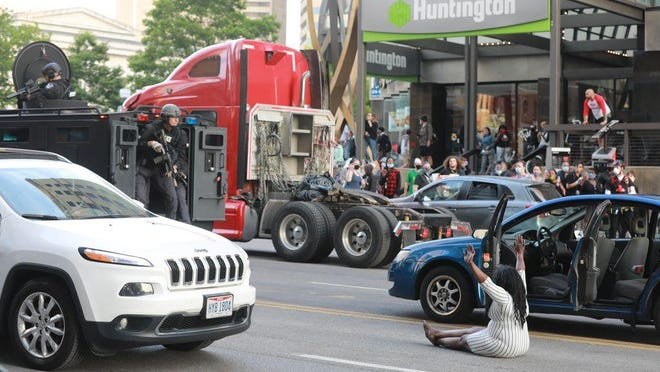 As police began to clear the protesters during the George Floyd protests around the Ohio Statehouse building in Columbus on Sunday, May 31, a woman drove her car toward a SWAT vehicle and then got out and sat down on the pavement.