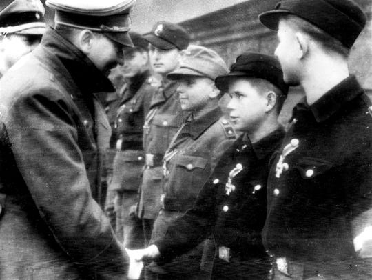 Adolf Hitler, left, shakes hands with 12-year-old Alfred