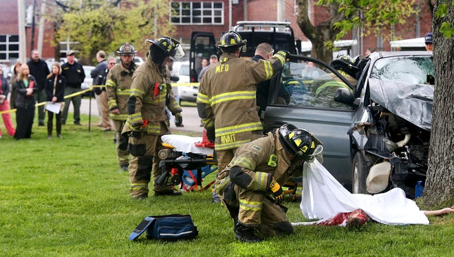 Fire Capt. William McAdoo checks on Matthew Conners, who portrays a wreck fatality, during a mock crash scenario to deter drunken driving. Central Magnet School students watch in the background on Thursday.
