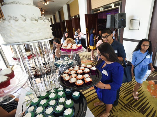 Event attendees circle the cupcake samples by Laling's