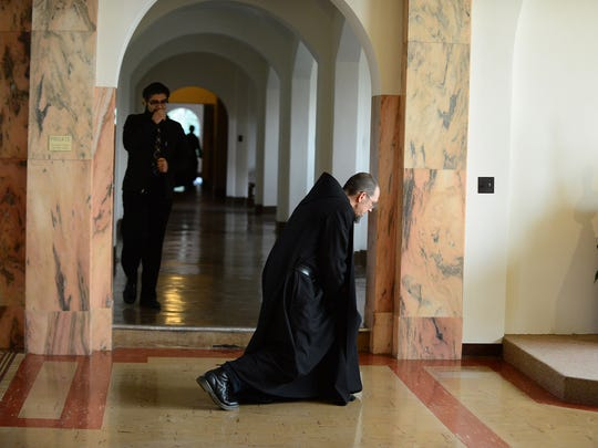 Brother Andre Love, a Benedictine monk, kneels in the church after praying at the Mount Angel Abbey. Love is curator of the Abbey's art collection.