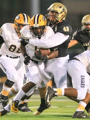 T.L. Hanna's Anthony McCarthy (42) tackles Greenwood's Roshun Jackson during the first quarter at T.L. Hanna High School in Anderson.