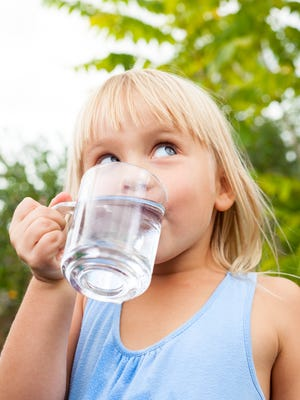 Young girl drinking water.