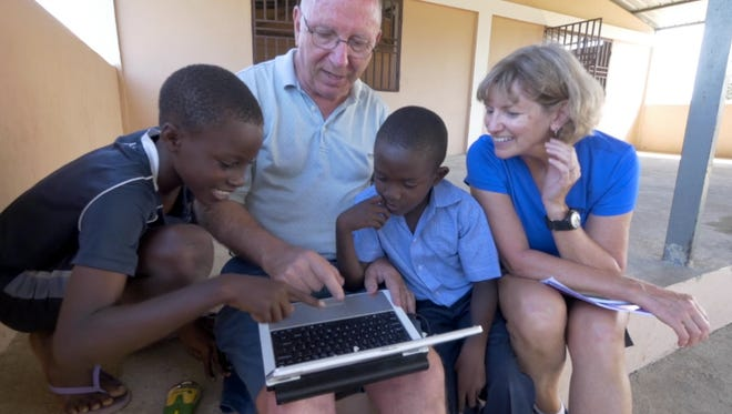 Denny Baumann demonstrating a math game with children and a mission team volunteer in Cap Haitian, Haiti.