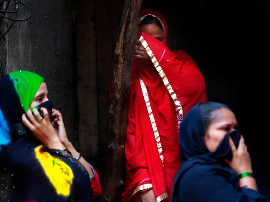Sex workers cover their faces from cameras as they