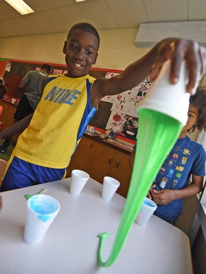Hezekiah Cochran, age 8, made slime during a science lesson Wednesday morning during the summer program at UMADAOP on Trimble Road.