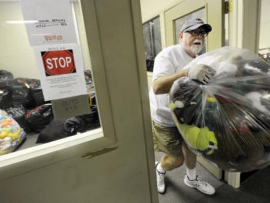Dave Brady, the chairman of the York County Toys for Tots carries a bag of stuffed animal out of a storage area located in Springettsbury Township on Saturday, July 25, 2015. The organization needed to move their toys to a new location in West Manchester Township when the space they were using was sold.