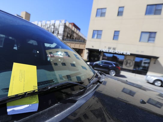 A parking ticket on the windshield of a truck parked