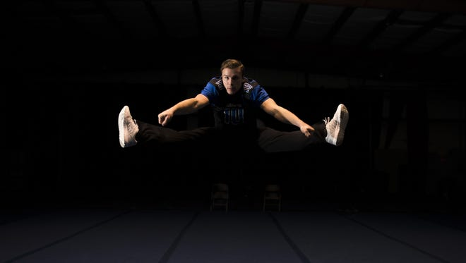 Hammonton senior Sean Ryker, 18, performs a toe-touch as he poses for a portrait Tuesday, Oct. 31, 2017 in Atco. Ryker is a competitive cheerleader as well as a running back for the Hammonton football team.