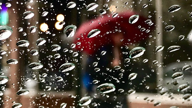 A file photo showing a man walking with a red umbrella through the rain in downtown Reno.