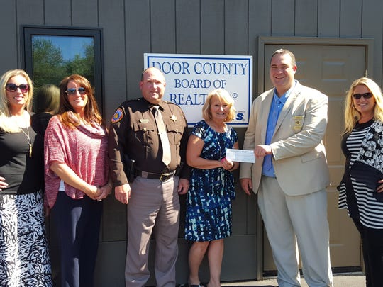 Pictured left to right: Bridgett Starr, Gina Sund, Sheriff Steve Delarwelle, Heidi Neubauer, Officer Chris Neuville, and Holly Tlachac. Committee members not pictured: MaryKay Shumway, Julie Henkel, and Paul Dreutzer.