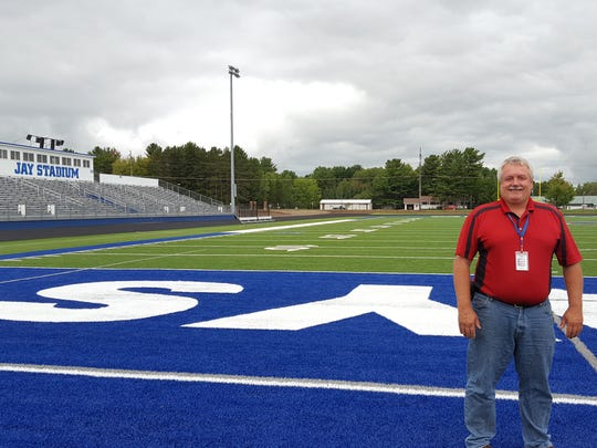 Building and Grounds Supervisor Dale Bergman poses for a photo on the new artificial turf at Merrill High School's renovated Jay Stadium on Sept. 7, 2016.
