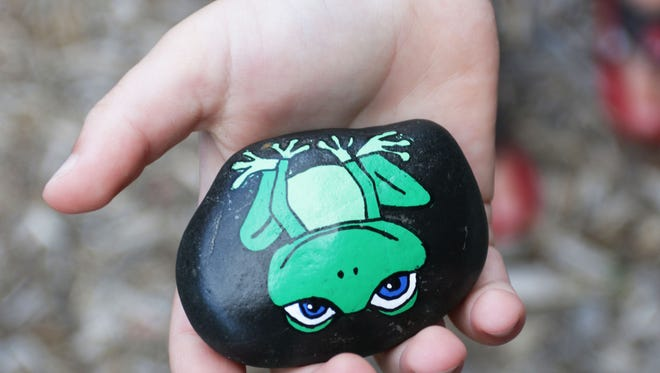 A child holds a painted rock Tuesday at Deland Park in Sheboygan.