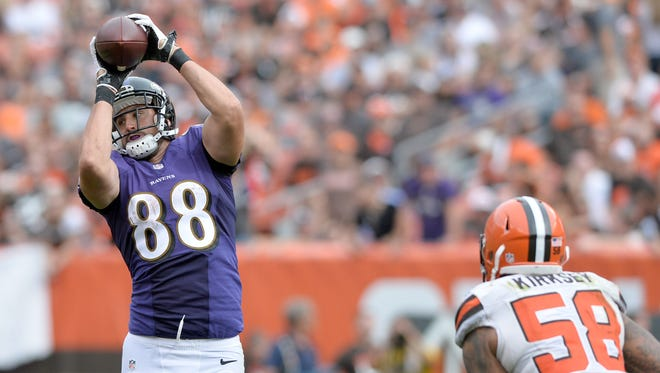 Baltimore Ravens tight end Dennis Pitta (88) catches a pass over the defense of Cleveland Browns inside linebacker Chris Kirksey (58) during the second half at FirstEnergy Stadium.