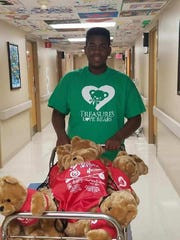 Gregory Thaxton pushes a cart of teddy bears down the