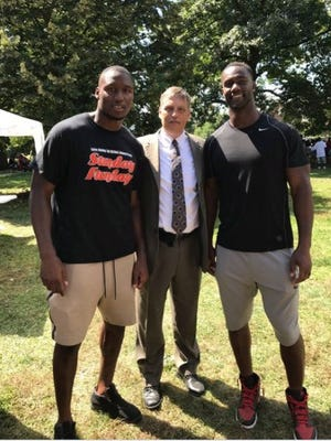 Carlos Dunlap and Michael Johnson pose with a representative from Cincinnati Domino's, which provided pizza for their Sunday Funday Back to School event at Laurel Park.
