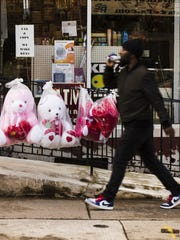 A pedestrian passes Valentine's day stuffed animals