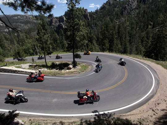 In this photo taken July 30, motorcycle riders make their way around one of the hairpin turns on state Highway 87 outside Sylvan Lake near Hill City, S.D.