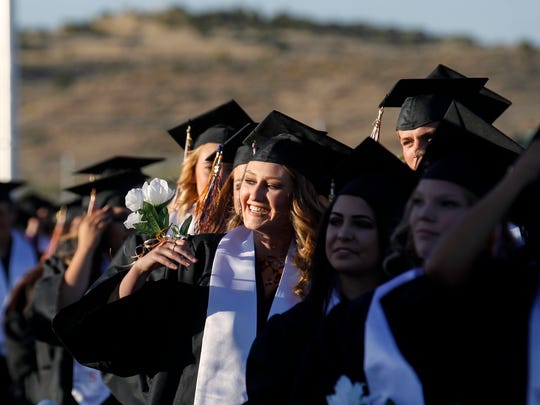 Aztec High School graduates enter Fred Cook Memorial Stadium on Friday for their high school graduation cerermony in Aztec.