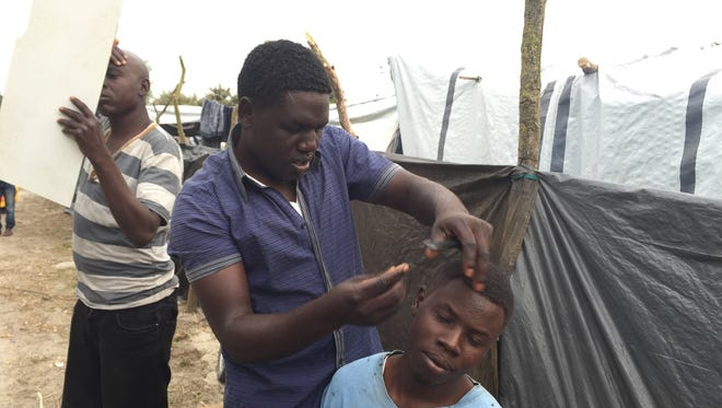 A barber cuts hair at the migrant camp in Calais, France.