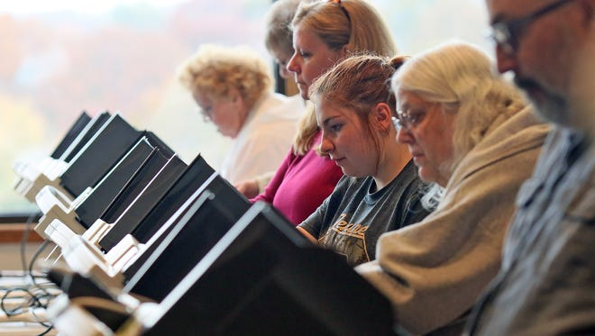 Lacie Arnold, 18, third from right, votes in her first presidential election Tuesday afternoon at Emmanuel Lutheran Church in Coshocton.