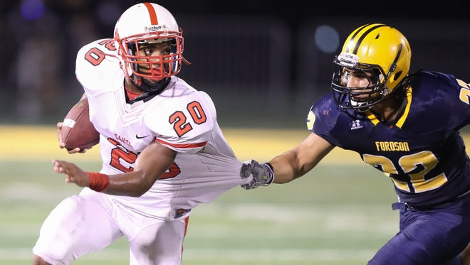 Canton's Julian Thornton is tackled by Dearborn Fordson's Ali Salman during the second half of Fordson's 40-35 win Friday at Wayne State.