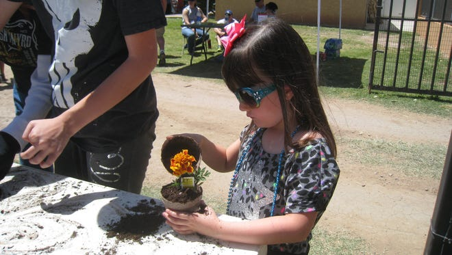 A child from Tularosa planting a flower for Earth Day 2015.