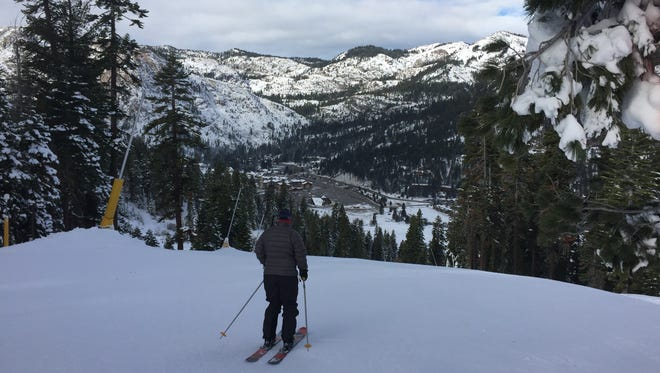 A skier overlooks the base of Squaw Valley Resort in December, 2015. Resort owners want to power the resort and surrounding community entirely by renewable energy by the end of 2018.