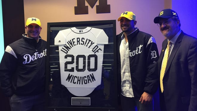 (From left) Tigers catcher James McCann, third baseman Nick Castellanos and University of Michigan president Mark Schlissel pose during the Tigers' visit to Michigan Stadium Friday.