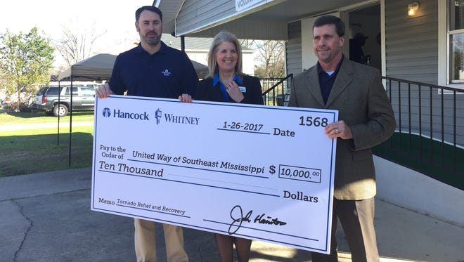 Hancock Bank donated $10,000 toward tornado recovery efforts. Pictured are Hancock Bank representatives Greg Hodges, left, and Keith Williams with United Way Director Tracie Fowler.