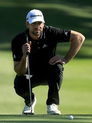 Aaron Rodgers lines up a putt on the 16th green during