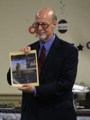 Mike Weber holds up his keepsake book from the Hales