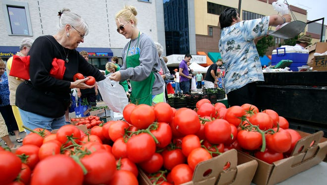 Madesyn Arena (center) assists a customer with a tomato purchase from her grandparent's business, Howard's Produce of Hortonville, during the downtown Appleton Farm Market on June 21.