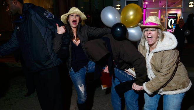 Jessica Douglas receives some help from Paul and Gracie Downs in pulling off some tight boots a NYE party. Thousands of revelers celebrate NYE with a ball-drop at Fourth Street Live on Tuesday night January 1, 2014