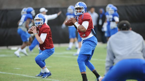 Junior QB Jalen Whitlow (center) and Freshman QB Drew Barker run a drill during a University of Kentucky football spring practice at the Nutter Training Facility in Lexington, KY. Wednesday, April 2, 2014.