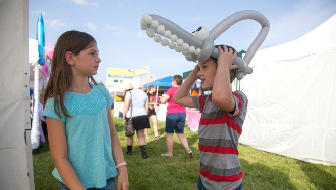 Lydia Sergent, age 9, watches as her brother Conner York, age 8, tries on his new shark hat made of balloons. Aug., 21, 2014