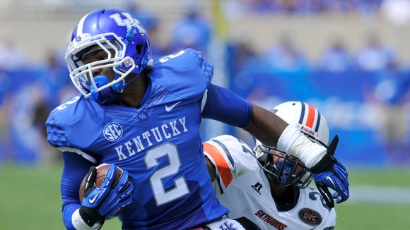 UK's Dorian Baker breaks a tackle against UT Martin's Jordan Landry, Saturday, Aug. 30, 2014 at Commonwealth Stadium in Lexington. Photo by Tim Webb, Special to the CJ