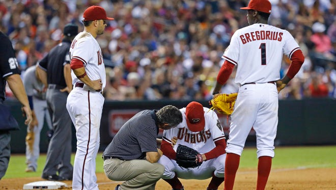 An Arizona Diamondbacks trainer checks on pitcher Brad Ziegler after he was hit by a line drive  in the eighth inning against the Detroit Tigers at Chase Field on Tuesday, July 22, 2014 in Phoenix.