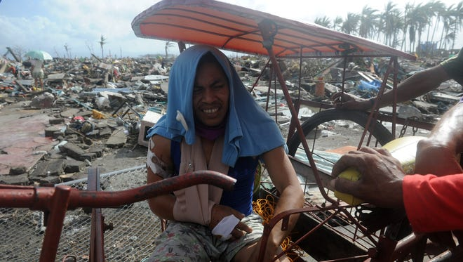 A flood survivor rests on a pedicab surrounded by debris caused by Typhoon Haiyan in Tacloban on Leyte island on Nov. 11.