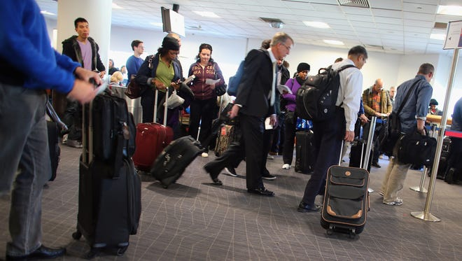 Passengers wait to board their plane at a terminal in LaGuardia Airport in New York.