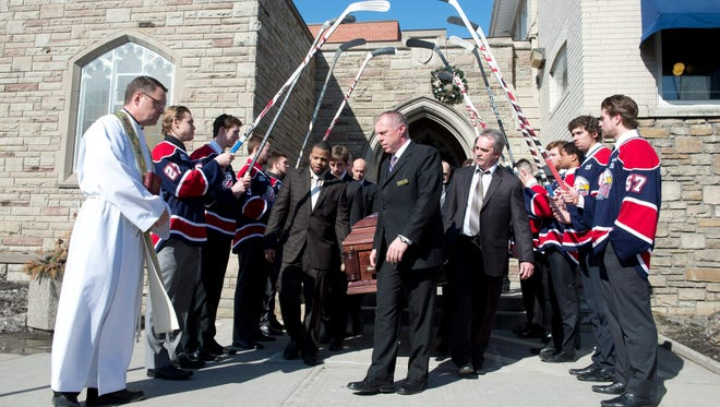 Saginaw Spirit hockey players hold up sticks as pallbearers carry the casket of teammate Terry Trafford after his funeral service on March 18.